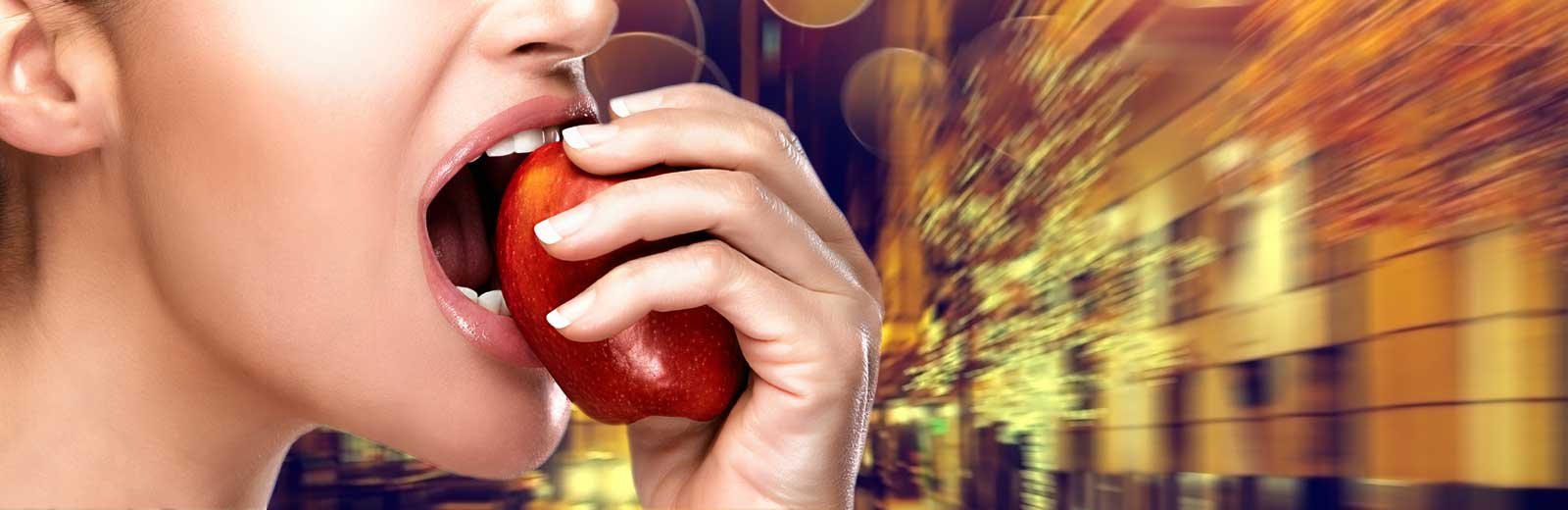 Young woman biting into an apple outside Gateway West Loop.