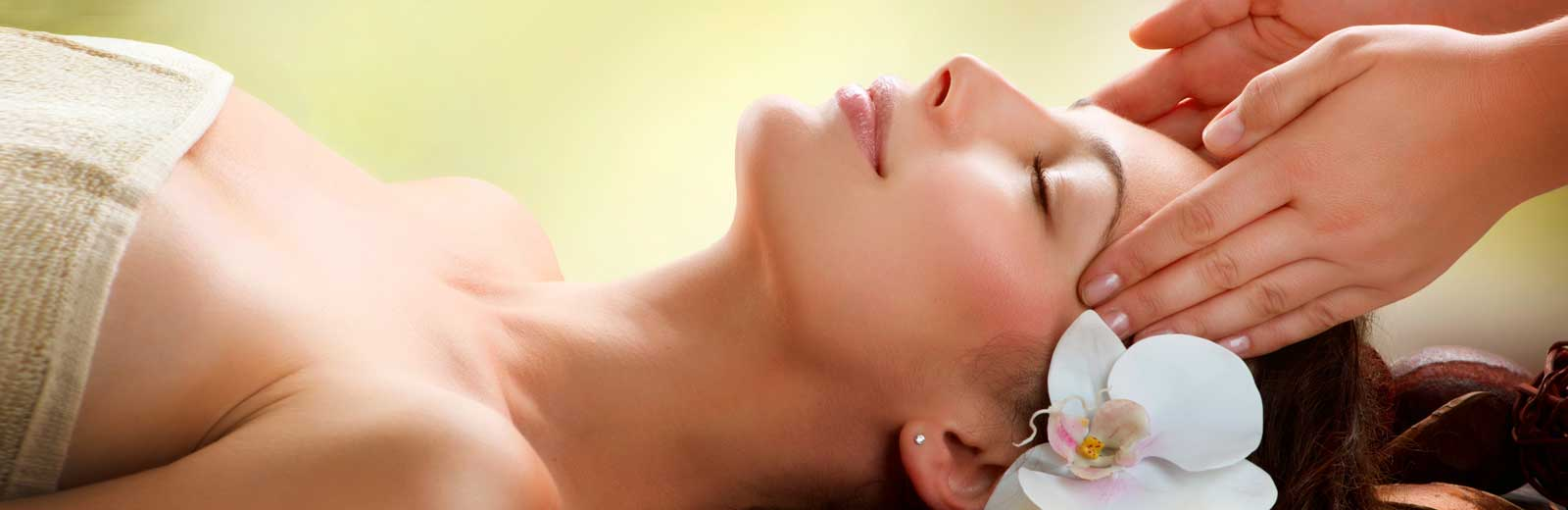 Beautiful woman with a fresh flower in her hair enjoying a massage.