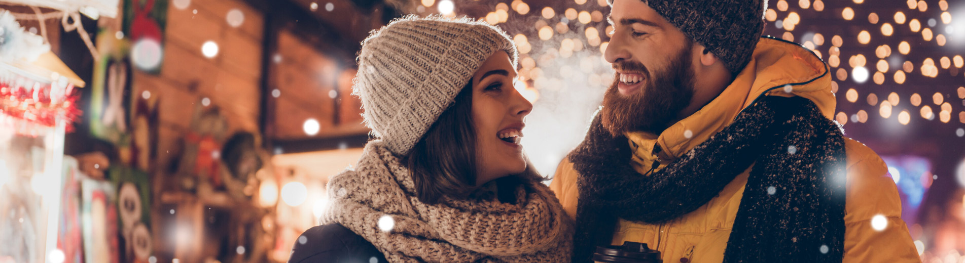 Warmly dressed happy young couple smiling at each other with holiday lights behind them.